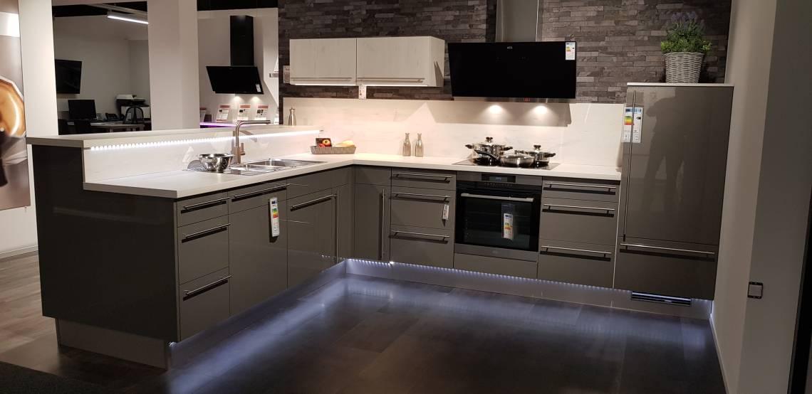 Dies ist ein Foto einer modernen Hochglanzküche in L-Form mit vielen Leuchten